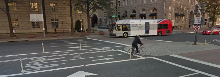 Google Streetview Image of Pennsylvania Ave bike lanes with intersection showing crossing sign